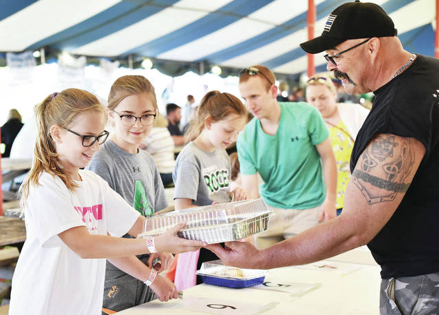 McKinley Schloss, left, 10, daughter of Scott and Amber Schloss, is handed a cake by Anna firefighter Michael Wade, both of Anna, at Anna Homecoming Festival Friday. McKinley won the cake at the Anna Fire Department's cake wheel.