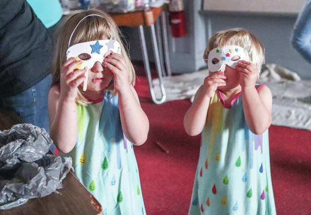 Aleria Stock, left, 5 and her sister Daelyn Stock, 3, both of Sidney, children of Carrie Stock, try on the masks they made in the Kids Arts Zone which was held as part of the Back Stage Block Party at the Historic Sidney Theatre Saturday, June 15.