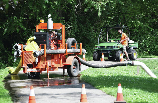 City of Sidney employee Jeremy Dearth, of Sidney, checks on a pump that was pumping water out of Custenborder Field and back into the Great Miami River Wednesday, June 19.