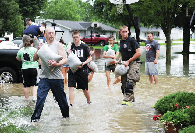 Botkins firefighters and volunteers carry sandbags to put around windows that lead into the basement of a house surrounded by flood waters at the intersection of Mary Street and South Sycamore Street in Botkins Wednesday, June 19. Seven streets were closed off in Botkins after heavy rains once again flooded the town this summer.
