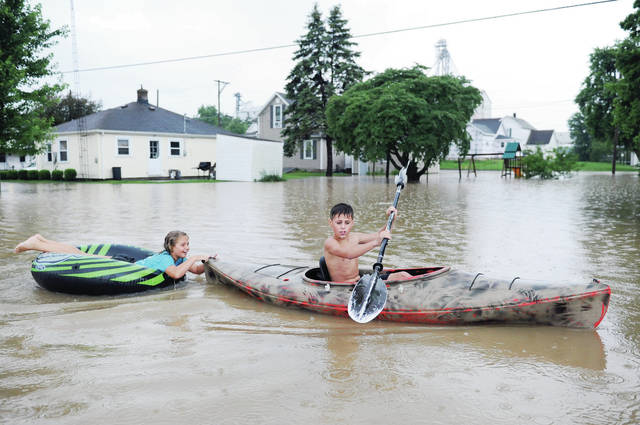 Damien Leugers, right, 12, padals his kayak with his sister, Kaydence Duncum, 9, both of Bokins, in tow through the flooded yard of Ron and Diane Meyer, located on West Walnut Street in Botkins Wednesday, June 19. Seven streets were closed off in Botkins after heavy rains once again flooded the town this summer. The siblings are the children of Jennifer and Brad Duncum.