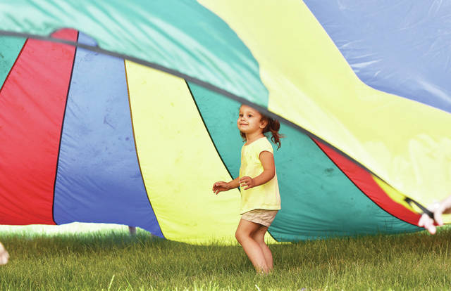 Courtney Ratermann, 2, of Sidney, daughter of Todd and Emily Ratermann, runs under a parachute at the Holy Angels Catholic Church annual Parish Picnic Saturday, June 22.