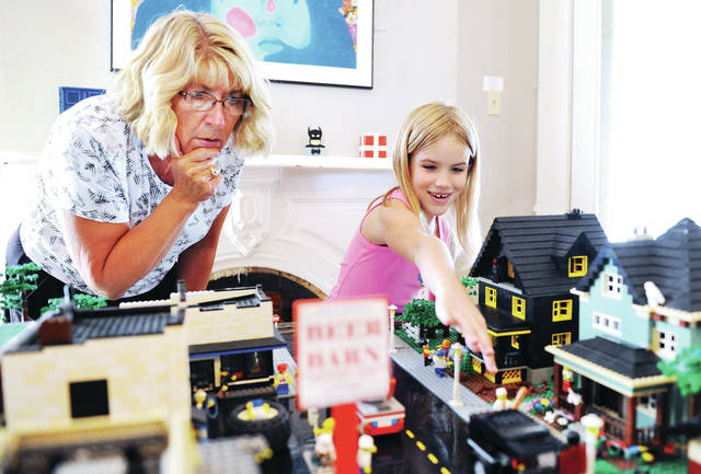 "Michelle Schneider, left, of Sidney, looks closely as her granddaughter Aubree Evans, 7, of Piqua, daughter of Alexa and Brad Evans, spots the ""man with a long loaf of bread"" in the LEGO display, It's All About That Brick, at the Gateway Arts Council Tuesday, June 25. There is a list of things people can try to find hidden in the display. The LEGO show ends this Friday."
