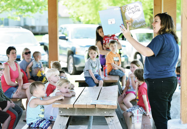 Amos Memorial Library employee April Orsborne, of Sidney, reads to kids at Plumridge Park on Wednesday, June 26. Orsborne was reading as part of Stories in the Parks hosted by Sidney Parks and Recreation. Kids also made paper hats.