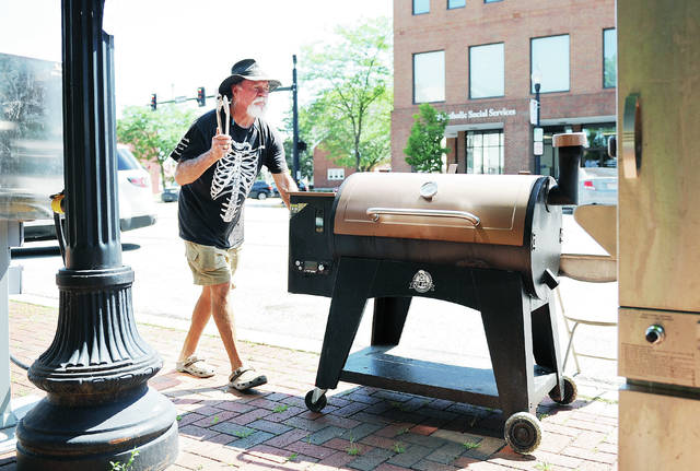 "Pin In or Pig Out owner Tim ""Tiki"" Reynolds, of Lake Okeechobee, Fla., pushes a grill into position on the courtsquare as he gets ready for The Great Downtown Sidney BBQfest Friday, June 28. Besides more traditional BBQ meat Reynolds will also be selling real alligator ribs. Reynolds travels from Florida up to Wisconsin on a regular basis selling his BBQ. The BBQ festival will be held from 11 a.m. to 10 p.m. Saturday, June 29."