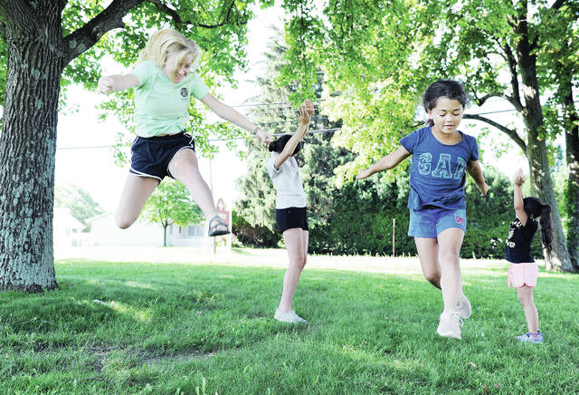 City of Sidney Parks and Recreation employees, left to right, Ciera Driskell, of Tawawa, and Emily Fogt, of Sidney, teach sisters Keygan Bladen, 9, and Myah Bladen, 6, both of Sidney, both the children of Tareena Bladen and Chad Bladen, some gymnastics moves at Orbison Park Friday, June 28. The gymnastics clinic is one of the ongoing events being put on by the Sidney parks department.