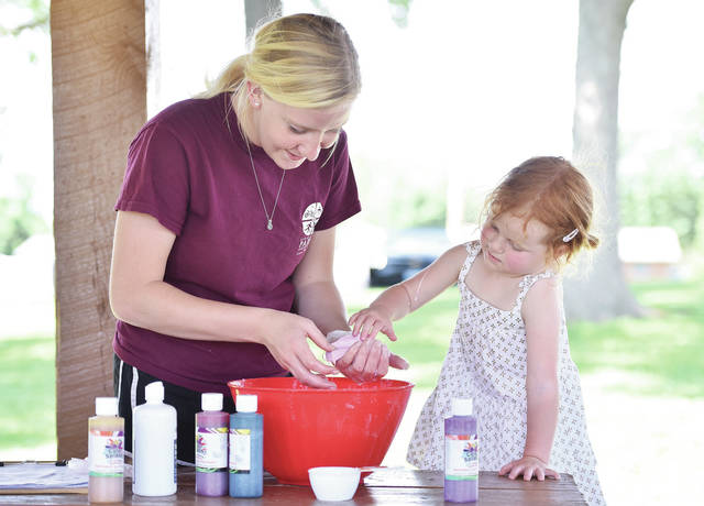 City of Sidney Parks and Recreation employee Ciera Driskell, left, of Tawawa, helps Ivy Adams, 3, of Sidney, daughter of Mindy and Alex Adams, make some pink slime at Deam Park on Wednesday, June 26. The slime project was one of the ongoing activities being held by the Sidney parks department.