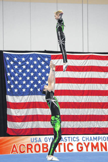 Alex Thompson, son of Misty and Josh Thompson, of Sidney, tosses Parker Slaven, son of Alton and Jennifer Slaven, of Sidney, in the air during their dynamic pair routine at acro nationals.