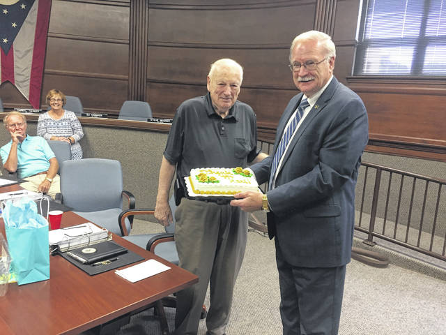 Civil Service Commission Chair Karl Bemus, front left, is pictured with Mayor Mike Barhorst after he was presented with a cake, a card and a gift to honor his 45 years of service with the city of Sidney. Commission members John Schmidt and Joyce Goubeaux look on in the back ground.