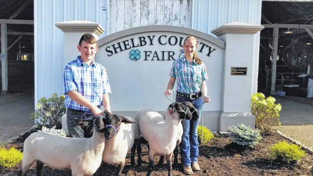 Carson and Keighlynn Rickert are shown with the lambs which were their 4-H project for the year. The siblings lost their sheep during a barn fire earlier this year.