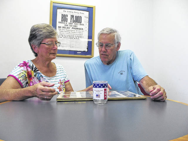 Wanda and Ron Challen, of Sidney, look through their wedding album. The couple exchanged wedding vows on July 20, 1969, the same day Neil Armstrong stepped on the moon. Sitting in front of the album is a moon glass that the Marathon gas stations gave away after the mission.