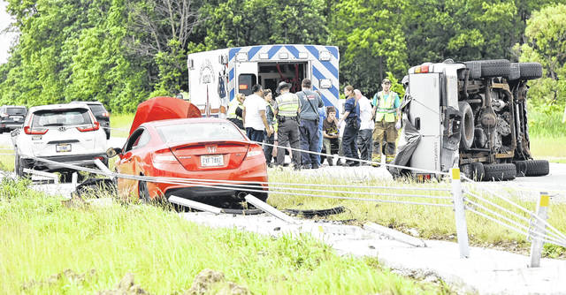 Emergency personnel look at injured drivers and passengers after a three-car crash June 9 near mile marker 98 on Interstate 75 near Anna. High tension cable barriers stopped two of the vehicles involved in the crash.