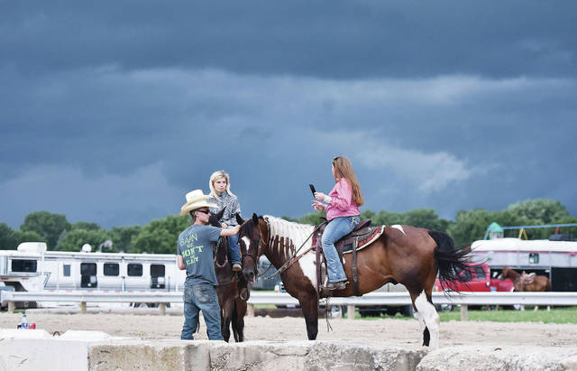 Storm clouds loom as, left to right, Trystan Hatton, of Middletown, Katie Deaton, of Lebanon, and Tessa Wells, of Middletown, hang out near the grandstand at the Shelby County Fair Sunday, July 21.