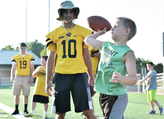 Sidney quarterback Cedric Johnson watches a child throw a pass during the program's 'Friday Night Lights' youth camp on July 13, 2018 at Sidney Memorial Stadium. This year's event has been canceled due to hot temperatures.
