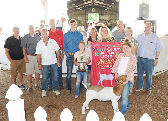 Norah Homan, of Botkins, daughter of Fred and Billie Homan, a member of Botkins Livestock, sells her reserve grand champion market goat at the Shelby County on Saturday, July 27. The goat sold for $1,875 an was purchased by 10 buyers.