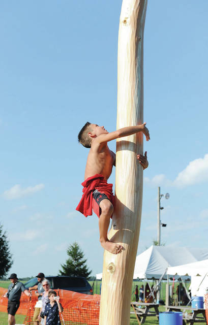 Bryce Lukey, 11, of Houston, son of Nathan and Veronica Lukey, climbs a greased pole in an attempt to reach money attached to it at the Kettlersville-Van Buren Twp. Fireman's Picnic on Saturday, July 20.