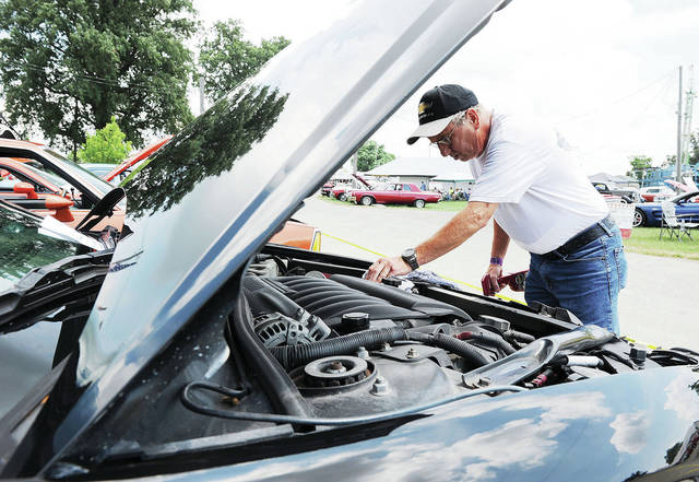 Dave Richards, of Houston, cleans the engine of his 2006 Monte Carlo Chevy SS on display at the 23rd annual cruise in at the Shelby County Fair Sunday, July 21.