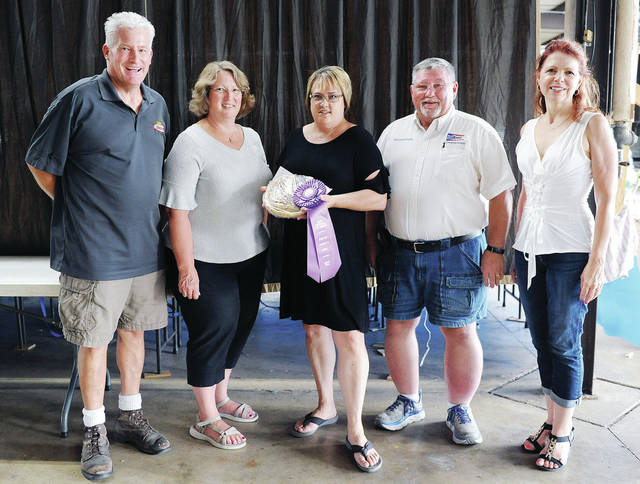 Lisa Spurgeon, center, of Sidney, sold her grand champion pie to, left to right, Shelby County Commissioner Tony Bornhorst, Clerk of Courts Michele Mumford, Shelby County Commissioners Bob Guillozet and Julie Ehemann, during the open class bake goods auction at the Shelby County Fair Sunday, July 21. Treasurer John Coffield and the Shelby County Republican Central Commitee were also part of the winning bid.