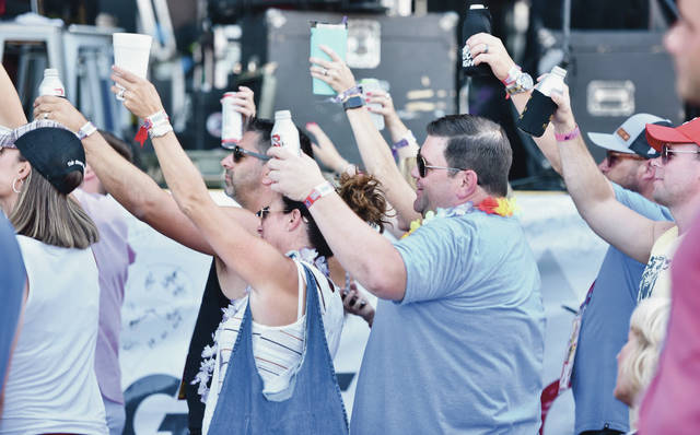 Fans raise their drinks in a toast requested by Chris Lane at Country Concert on Friday, July 12.