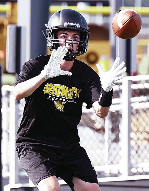 Sidney's Curtis Spangler reaches for a throw during a 7-on-7 scrimmage against Lehman Catholic on Thursday at Sidney Memorial Stadium.