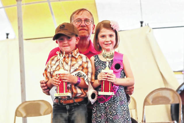 Gary Strasser, manager of Clancy's restaurant, is pictured with winners Oliver Bensman, 4, son of Randy and Sheila Bensman, of Sidney, who was named Shelby County Fair Little Mister of the Shelby County Fair, and Emma Bensman, 5, daughter of James and Tori Bensman, of Anna, who was crowned Shelby County Fair Little Miss of the Shelby County Fair Sunday night. The two young winners were cousins.