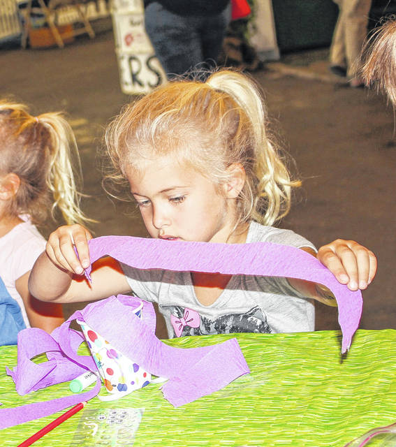 Aubrey Huelskamp, daughter of Doug and Rachel Huelskamp, of Sidney, works on her windsock at the 2918 Shelby County Fair in the FREE Fun with Crafts event.