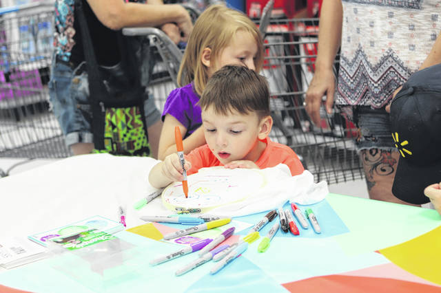 Tyler Bradley, 3, the son a Tiffany and Cody, of Sidney, makes a shirt on Saturday. Walmart put on a kids back to school again event from 9 a.m.-5 p.m. Saturday. Kids lined up to tie-dye shirts and get slime kits.