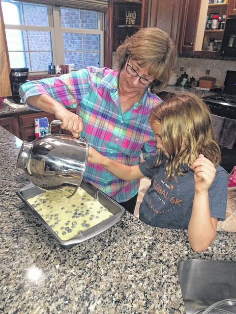 Peggy Roeth and granddaughter granddaughter Audrey pouring the batter.