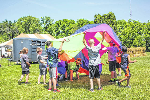 Campers played with a parachute during the Conservation Day Camp.