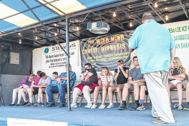 Volunteers react to what they perceive to be a foul smell during hypnotist Mike Bishop's show on Wednesday evening at the Shelby County Fair.