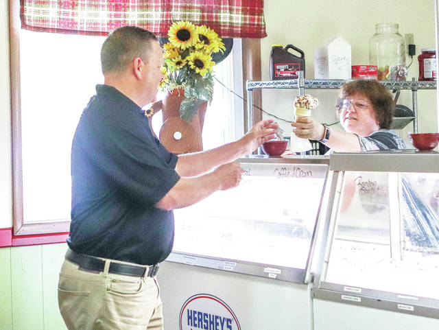 Joe Turner, left, Commercial account rep for NKTELCO, gets some ice cream from Amelia's owner Amelia Alexander during the ribbon cutting ceremony for Amelia's located at 1000 4th Avenue Sidney. The ribbon cutting was Tuesday, June 27.