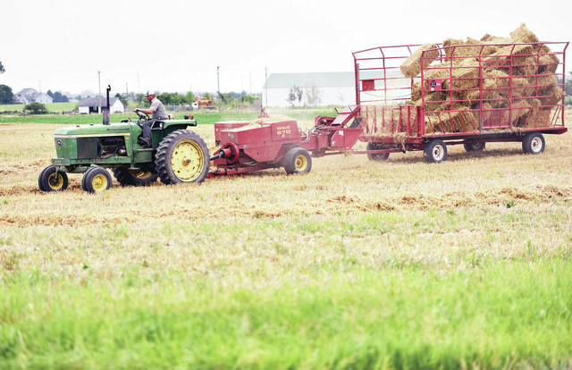 A farmer bales straw at the intersection of Sharp Road and State Route 29 on Saturday, July 6.