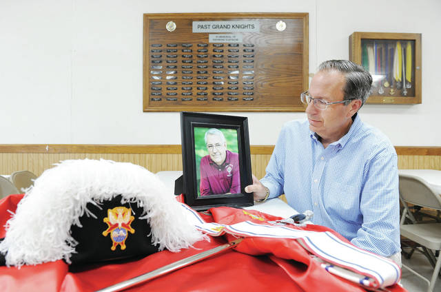 R. Michael Johnson sits with a photo of his dad at the Sidney Knights of Columbus Hall. Johnson was reinstalled as Grand Knight, 50 years after his dad was installed as Grand Knight. On the wall behind him is a board with the names of all past Grand Knights.