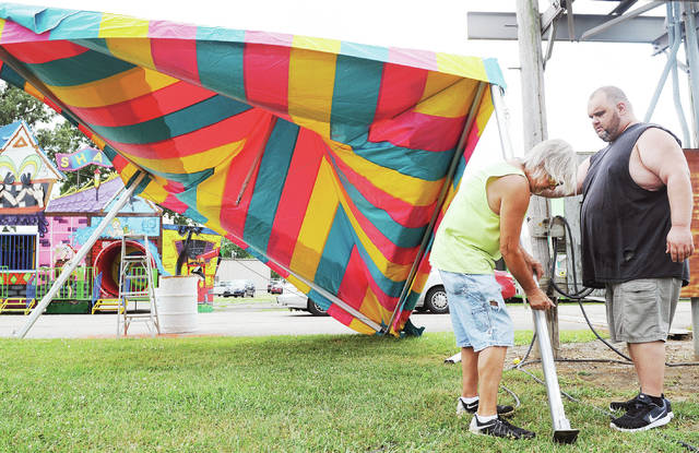 Jim Dyer, left, of Troy, and Tony Smith, of Tampa, Fla., setup a tent Wednesday, July 17, that will cover a washer toss carnival game during the Shelby County Fair. The fair runs from Sunday, July 21, through Saturday, July 27.