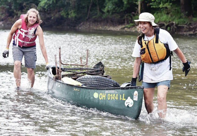 Shelby County Soil and Water Conservation District Education Coordinator Sophie Hurley, left, of Union City, and Marge Cantrell, of Sidney, haul in a canoe filled with garbage near a boat dock at Hussey's in Port Jefferson on Friday, July 19. The two pulled the garbage out of the Great Miami River during the 2019 Great Miami River Clean Sweep.