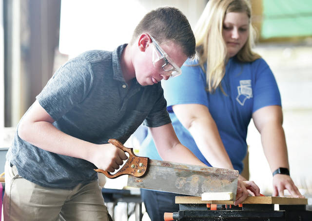 Carter Klopfenstein, 12, left, of Jackson Center, son of Darrel and Julie Klopfenstein, saws a piece of wood while Junior Fair Board Vice President Morgan Meyer, 17, of Anna, daughter of Greg and Krista Meyer, helps hold the board still. Carter was competing in the category of Measuring Up, Woodworking at the Shelby County Fairgrounds on Friday, July 19. Kids demonstrate their basic woodworking skills and are then judged on a piece they made at home. The 2019 Shelby County Fair begins Sunday, July 21, and runs through Saturday, July 27.