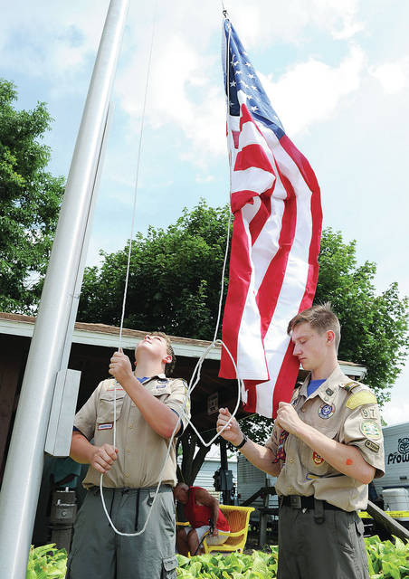 Boy Scout Troop 97 members Devan Wiford, left, 15, son of Rod and Dawn Wiford, and Gavin Musser, 14, both of Sidney, son of Tim and Kim Musser, raise the U.S.A. flag during the Shelby County Fair opening ceremony Sunday, July 21.