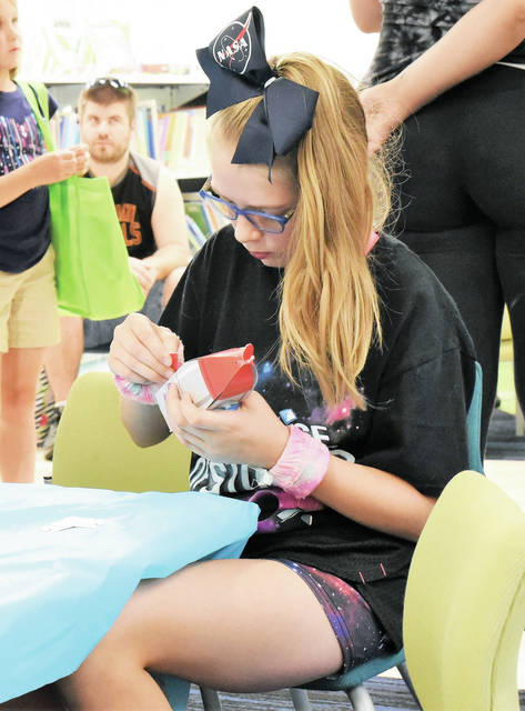 Laila Caudill, 11, of Sidney, focuses intently on building a cardboard rocket. Laila is the daughter of Brian and Charlene Caudill. The event was part of the Summer Library Program 2019 held Friday, July 19, in celebration of the 50th anniversary of the 1969 moon landing.