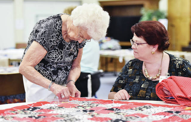 Margaret Cook, left, works on a quilt corner as Ohio Living Dorothy Love activities coordinator Lori Puterbaugh, both Ohio Living Dorothy Love residents, watches during a Community Quilt event in the Amos Center on Saturday, July 20.