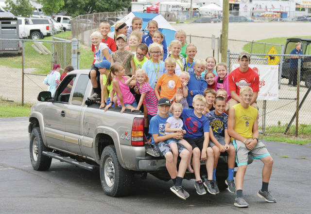 Thirty-five people in a pickup truck head for the entrance to the Shelby County Fair during carload night on Monday, July 22. The pickup was driven by Gina Poling, of Russia.