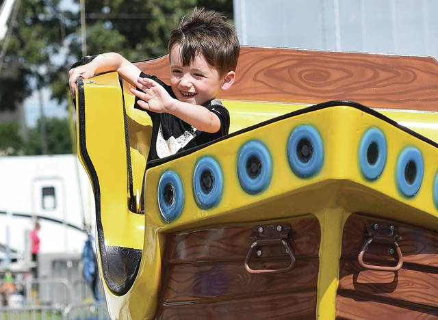 Niko Lyme, 4, of Sidney, son of Tammy Burnett and Brandon Lyme, waves to his grandma Brenda Goins from a pirate ship ride at the Shelby County Fair on Tuesday, July 23.