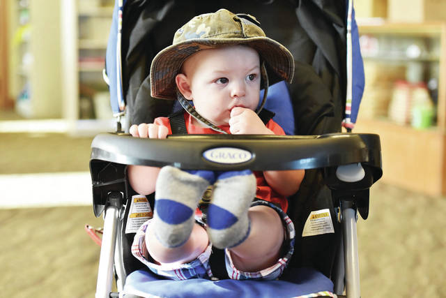 Wesley Geise, 11 months, of Sidney, son of Tyler and Susanne Geise, eats cheerios in the Shelby County Fair Secretary's Office at the Shelby County Fair on Tuesday, July 23.