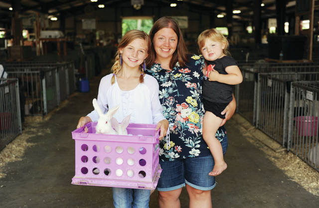Eliza Fullenkamp, left, 10, of Fort Loramie, sold her market rabbits for $1,700 at the Shelby County Fair on Friday, July 26. With her are her mom, Leah Fullenkamp, and her sister Greta Fullenkamp, 1, all of Fort Loramie. Buyers teamed up to purchase the rabbits in memory of Eliza's and Greta's father and Leah's husband, John Fullenkamp, who passed away after being rear-ended by a distracted driver.