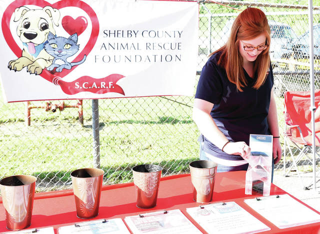 Dominique Christman, of Sidney, makes a donation Saturday, July 27 to The New Animal Shelter Shower. A drawing for prizes was held later in the day. Proceeds will go to caring for the animals.