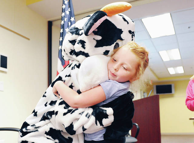 Charlee Guillozet, 5, of Sidney, daughter of Frank and Jessica Guillozet, gets a big hug from K & J's Ice Cream representative Molly the Moo Cow during Sidney Police Department's Safety Town 2019 held at the police department Wednesday, July 31. Kids learned how to be safe in a wide variety of dangerous situations such as becoming separated from their parents, finding themselves close to a dangerous animal or in the event of a fire.