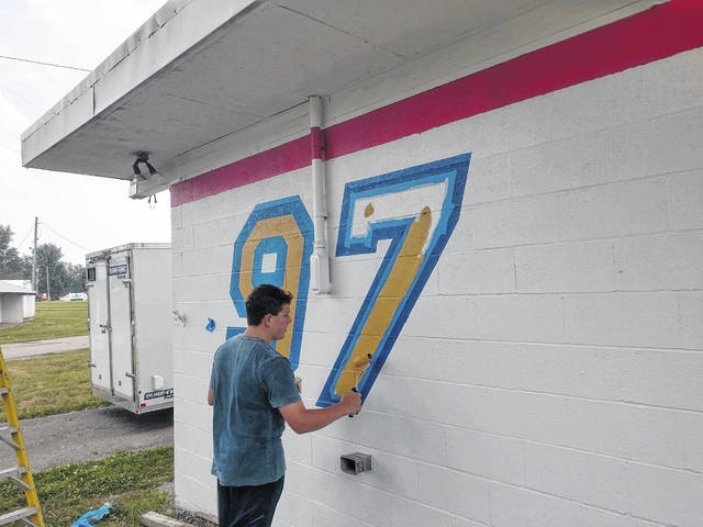 "Prior to the beginning of the Shelby County Fair, Boy Scout Troop 97 spruced up their building at the fairgrounds. The troop repainted the building a the Boy Scout emblem and a large No. 97 identifying the ""pop stand."" The scouts sell ice, pop, candy and snacks during the fair to help support Troop 97 activities. Assistant Scoutmaster Rod Wiford designed the new look for the building. Life Scout Devan Wiford, pictured, assisted his father in painting the artwork."