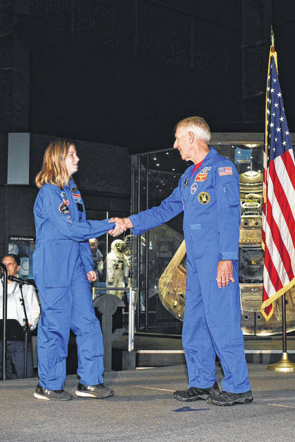 Cloe Crothers, 13, of Sidney, is congratulated by astronaut Bob Springer during graduation ceremonies from Space Academy in Huntsville, Ala.