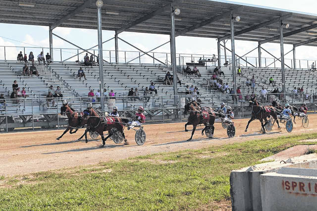 Horses and their drivers speed around the grandstand track at the Harness Races on Tuesday, July 23, and Wednesday, July 24 at the Shelby County Fair.