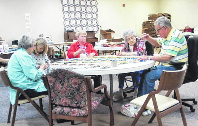 From right to left, Irene Thomas, Pam Bennett, Lori Puterbaugh, Polly Watkins, and Tom Watkins work on quilting projects at Dorothy Love.