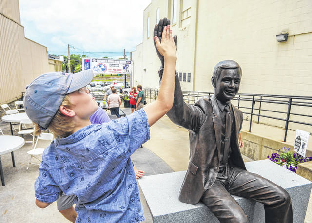 Nine-year-old Pax Martin, of Montana, high-fives a statue of Neil Armstrong during Wednesday's dedication of the Armstrong Homecoming Statue at Heritage Parkway in downtown Wapakoneta.
